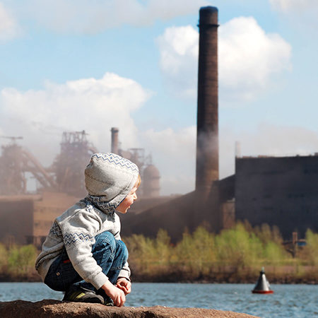 boy in front of coal plant